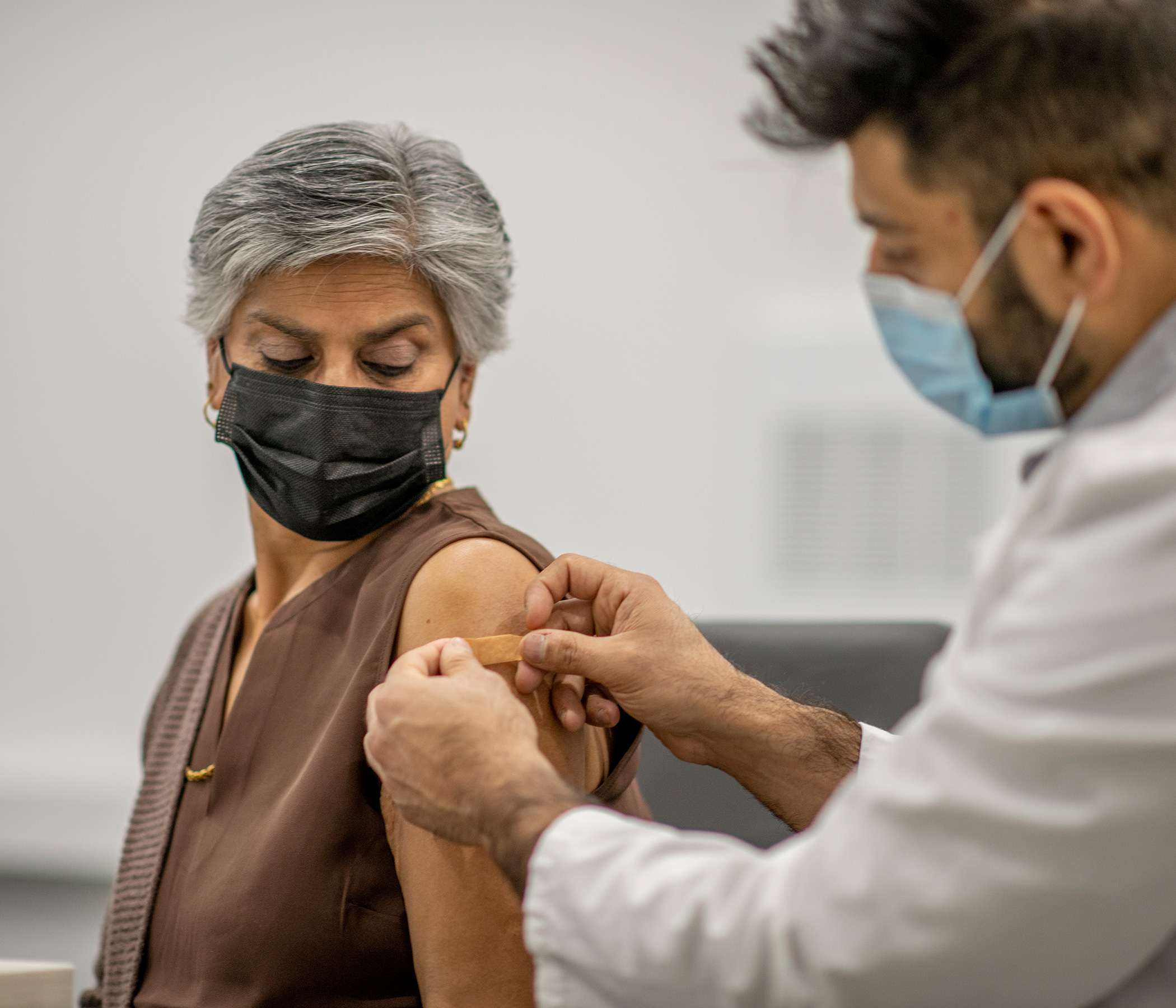 Older woman receiving a vaccination from a physician