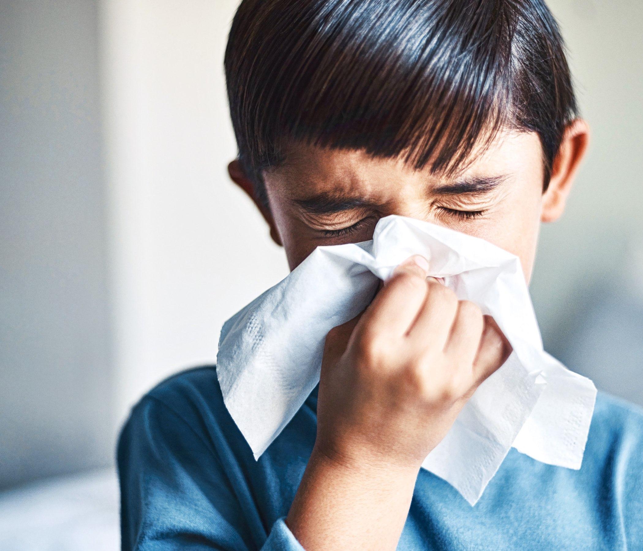 Tiro cosechado de un pequeño muchacho adorable que sopla su nariz mientras que está parado en su hogar