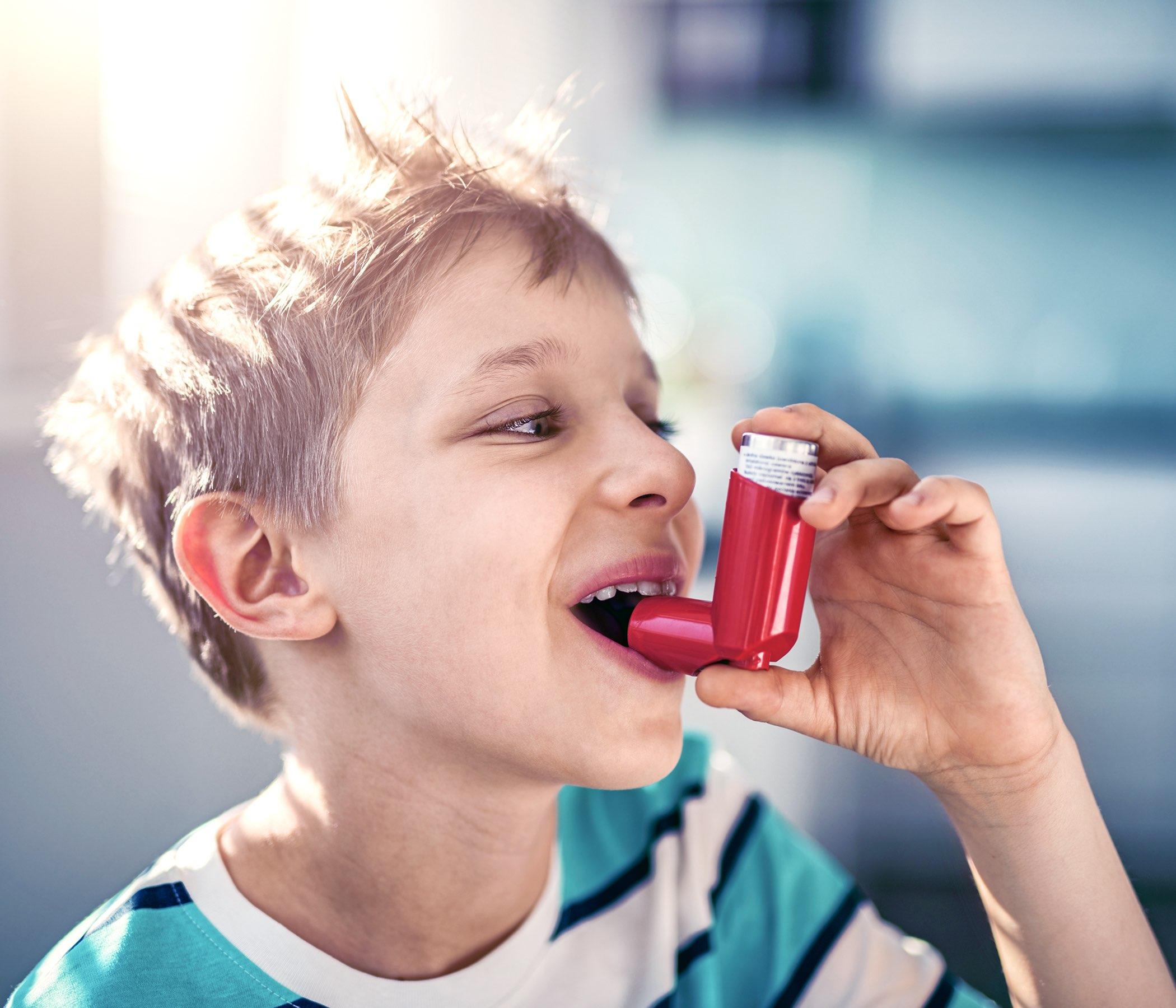 muchacho que usa el inhalador del asma