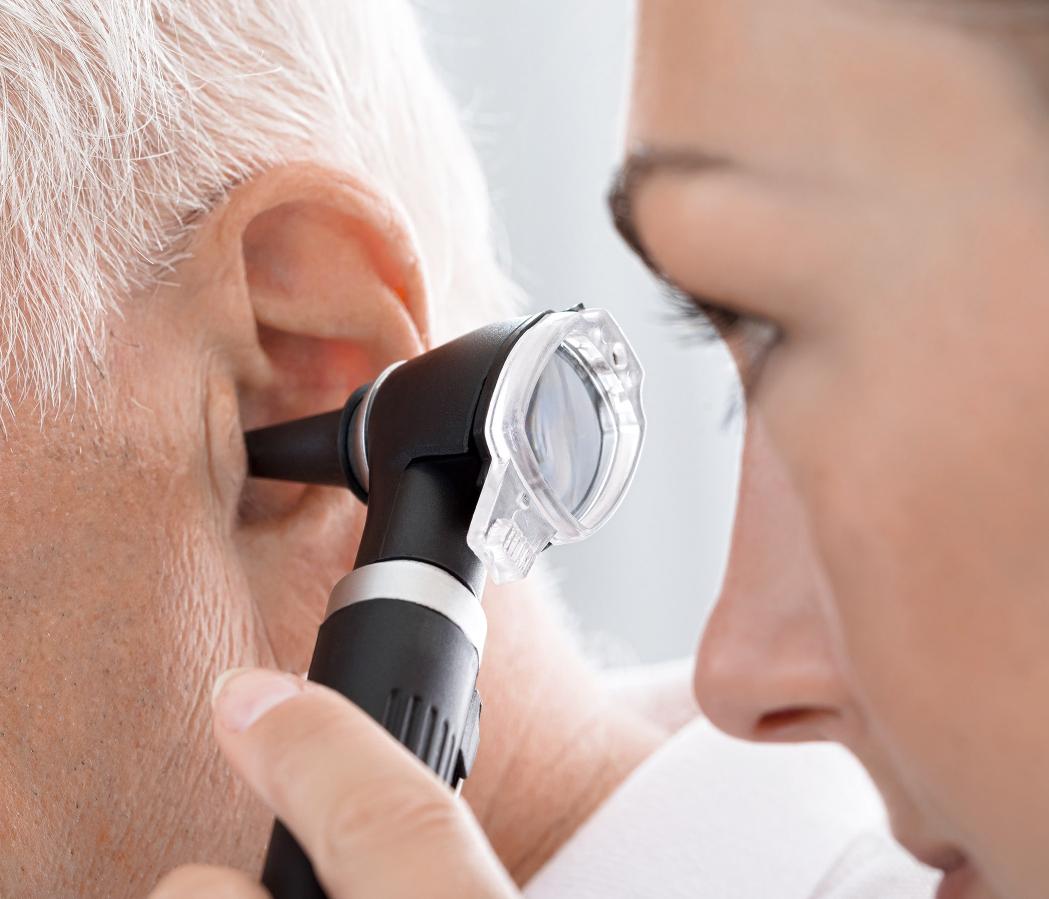 Female Doctor Examining Patient's Ear - stock photo Close-up Of Female Doctor Examining Patient's Ear With Otoscope