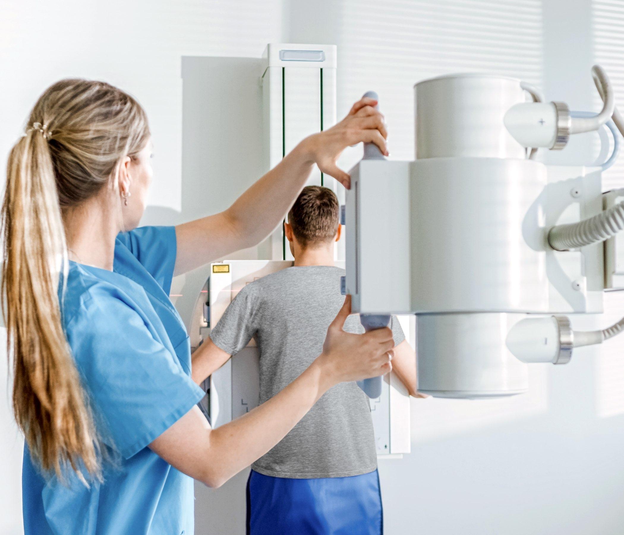 Cara derecha del hombre contra la pared mientras que el técnico médico ajusta la máquina de radiografía según la exploración