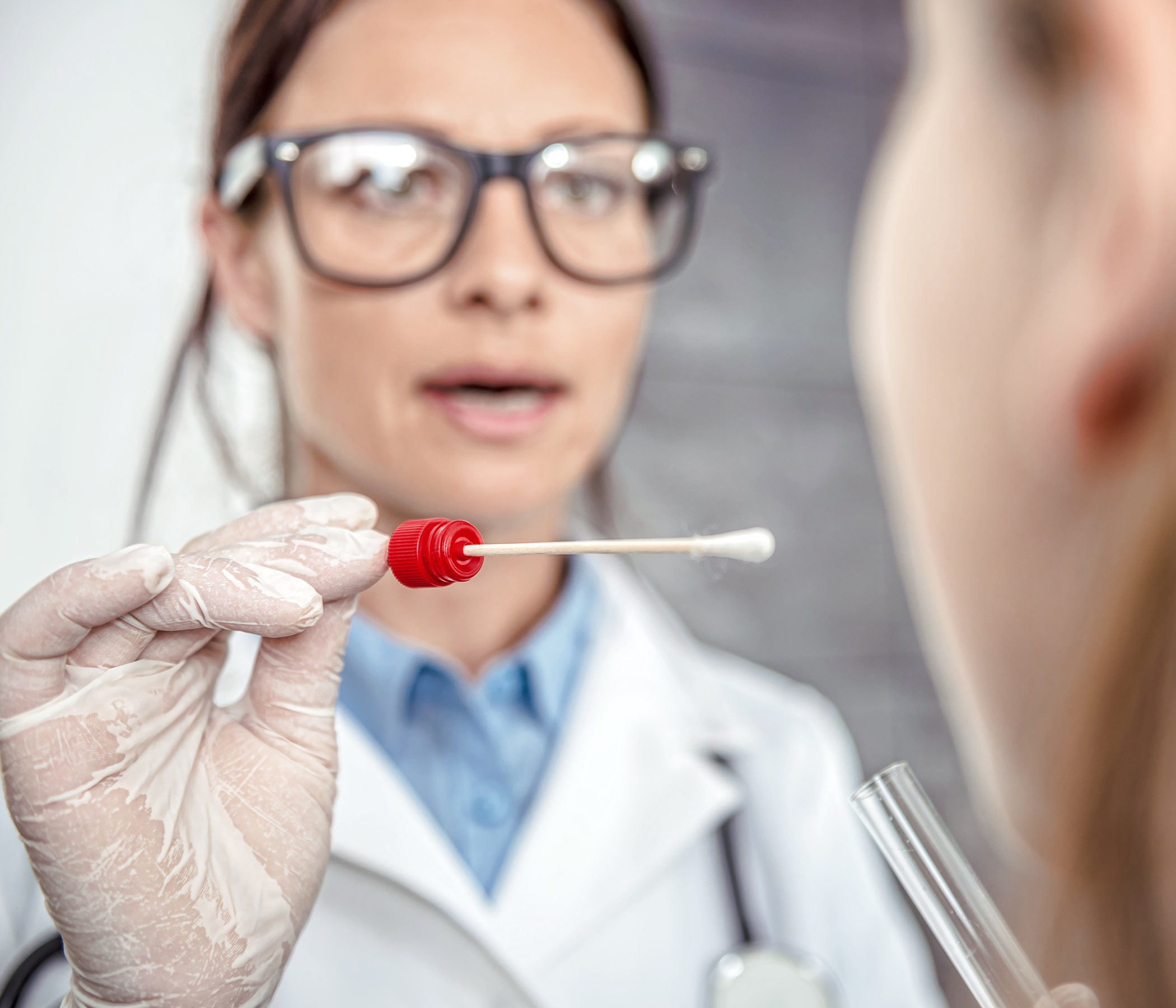 Pediatra femenino que usa una esponja para tomar una muestra de la garganta de un paciente