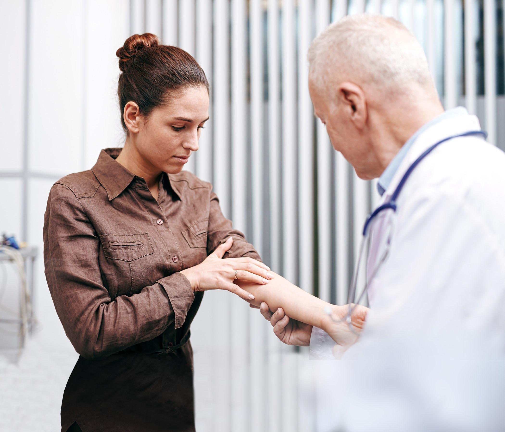 Mujer enferma joven que demuestra su brazo al doctor mientras que visita clínicas