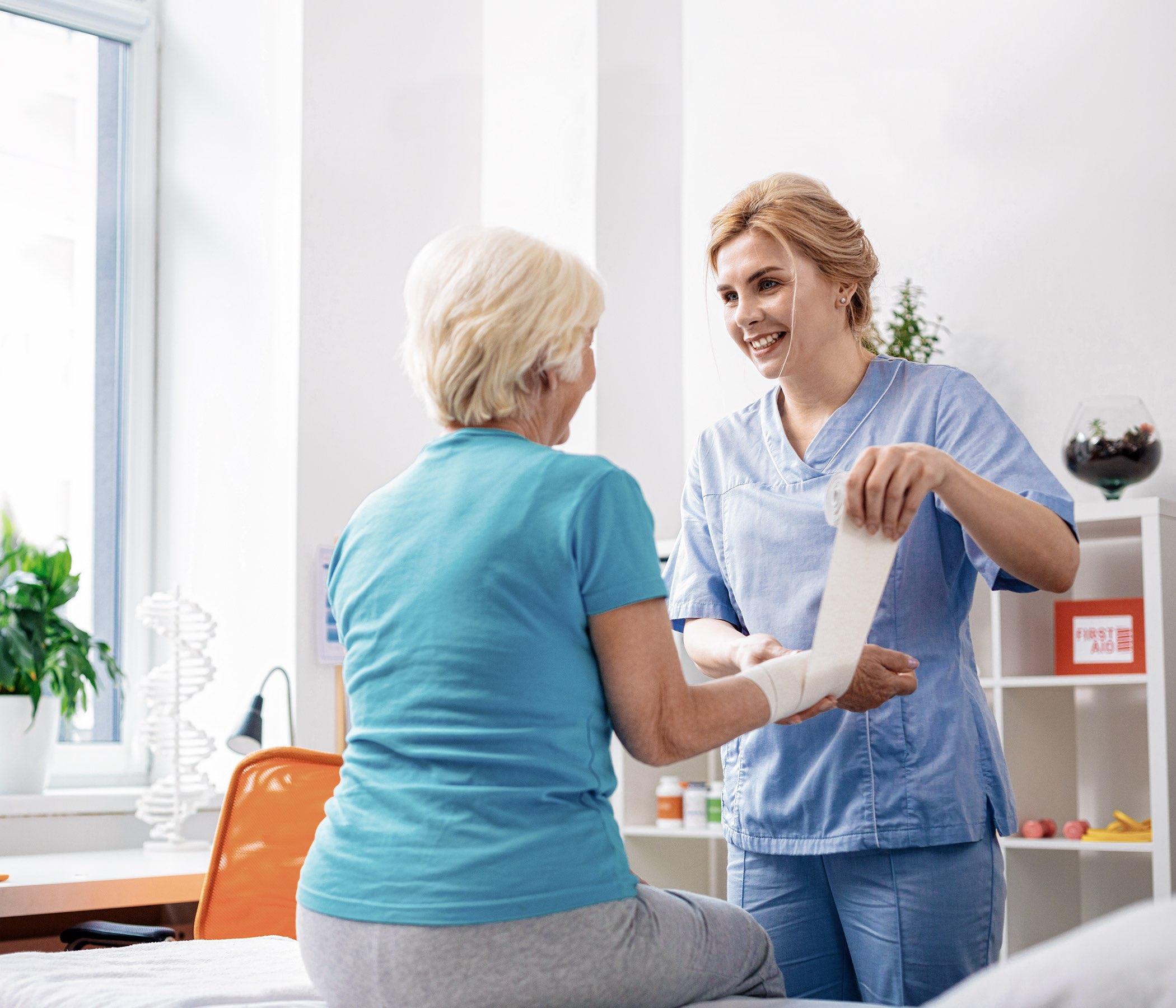 Enfermera femenina amistosa de Niza que sonríe a su paciente mientras que hace su trabajo en el hospital