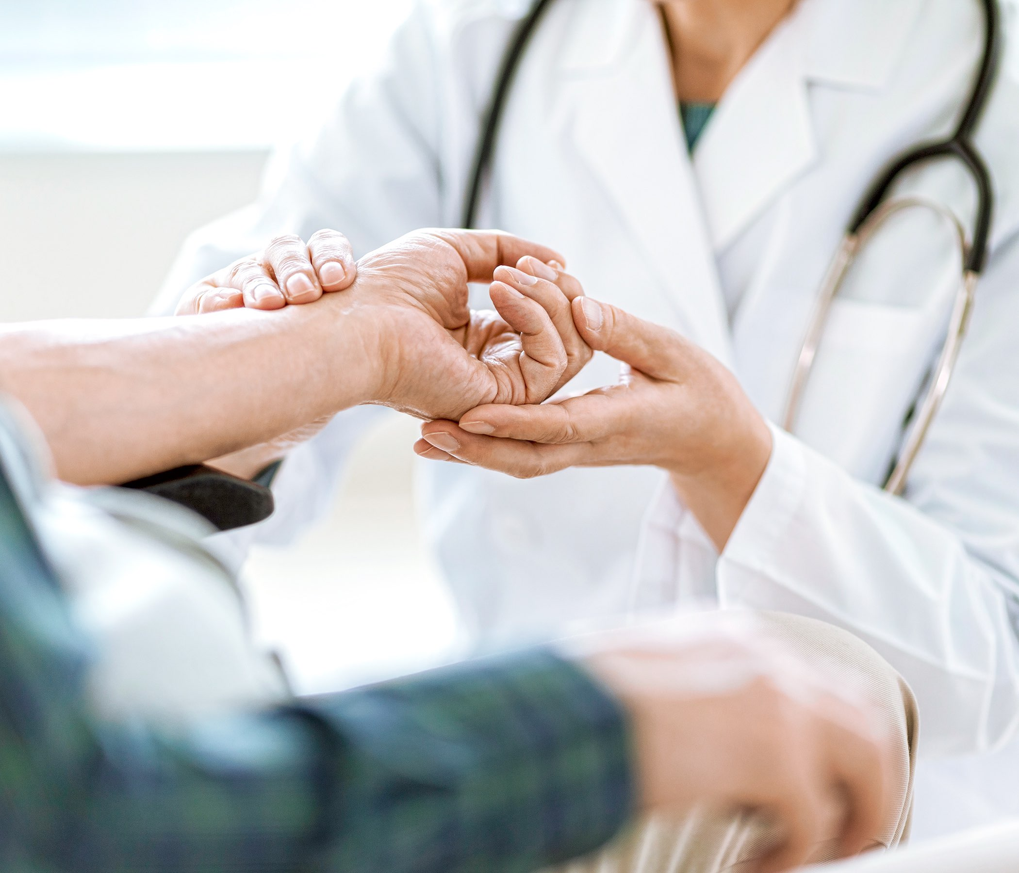 Doctor femenino que examina la mano del hombre mayor
