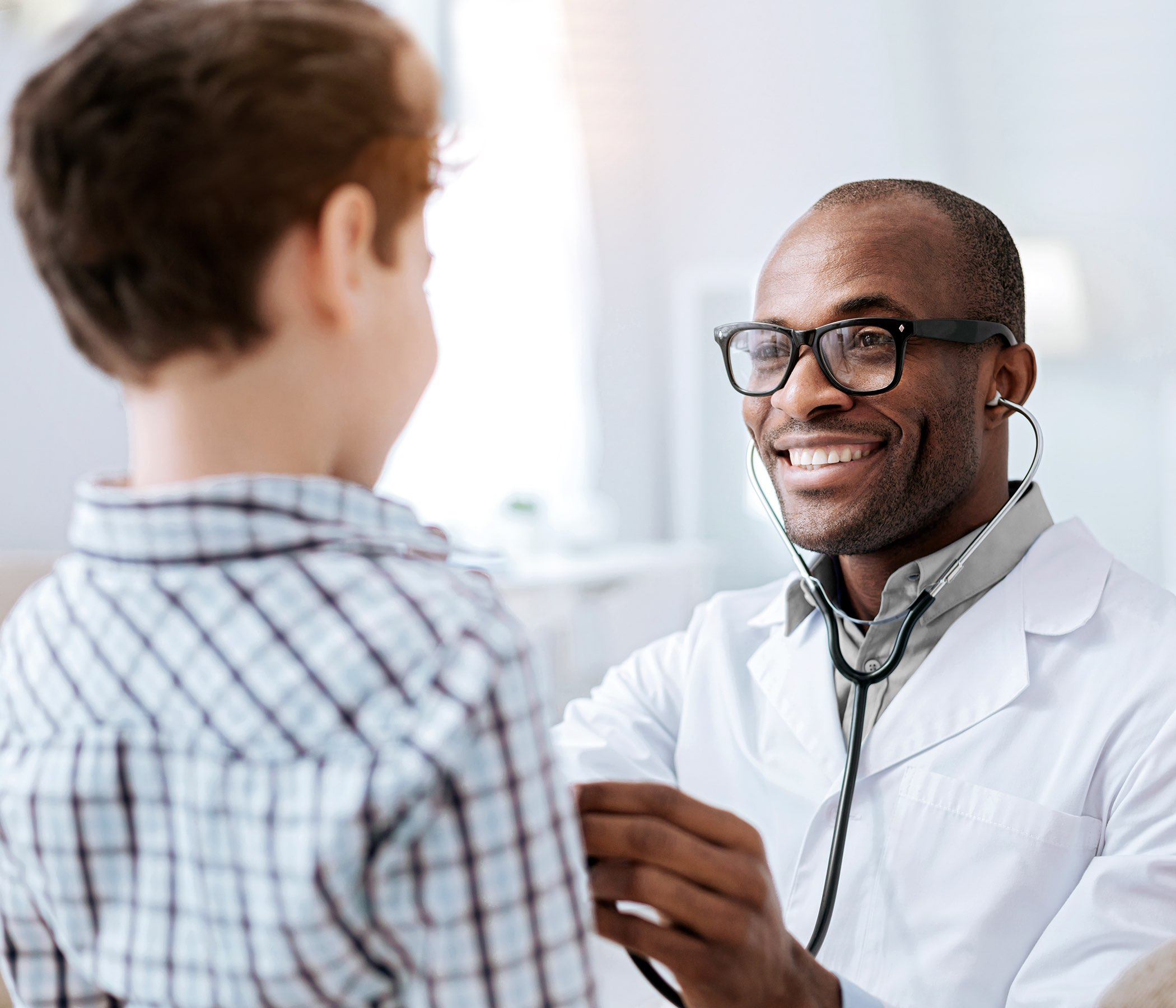 male doctor listening to boy while putting on glasses and using stethoscope