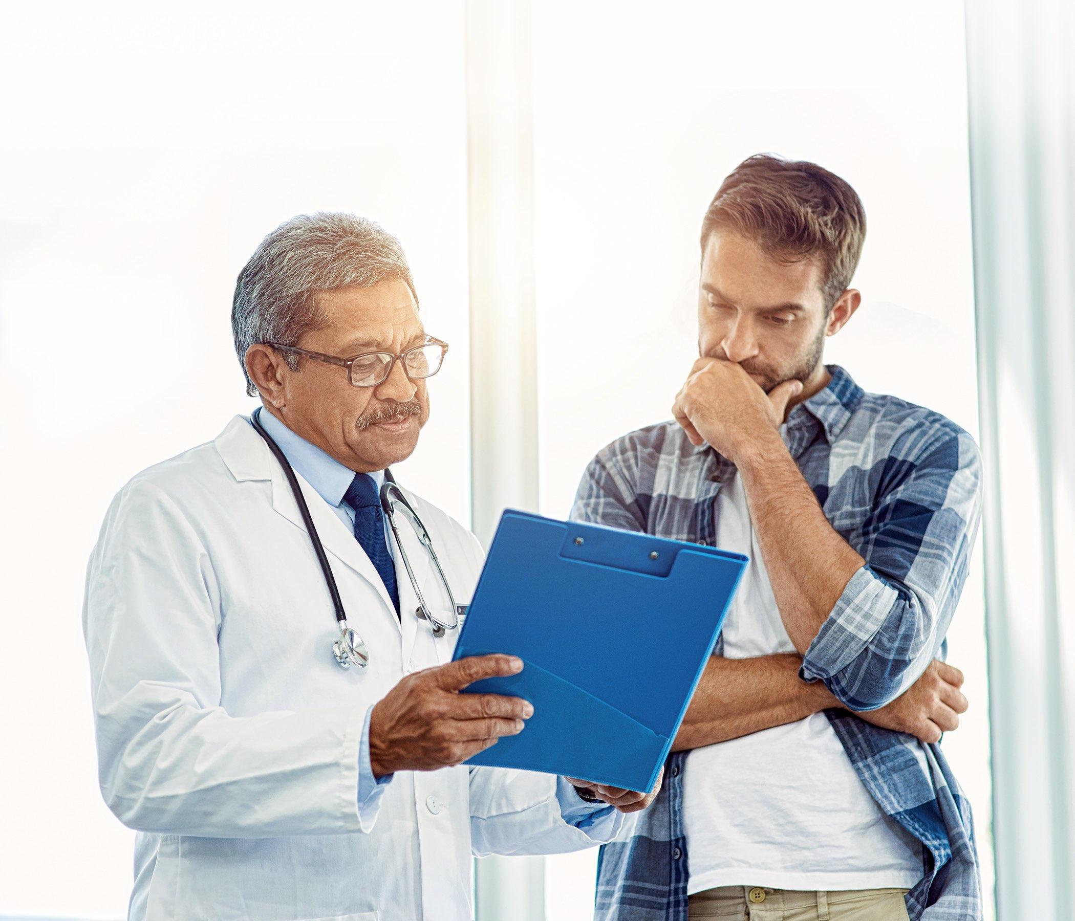 doctor masculino maduro que demuestra resultados de la prueba a un paciente dentro de un hospital durante el día