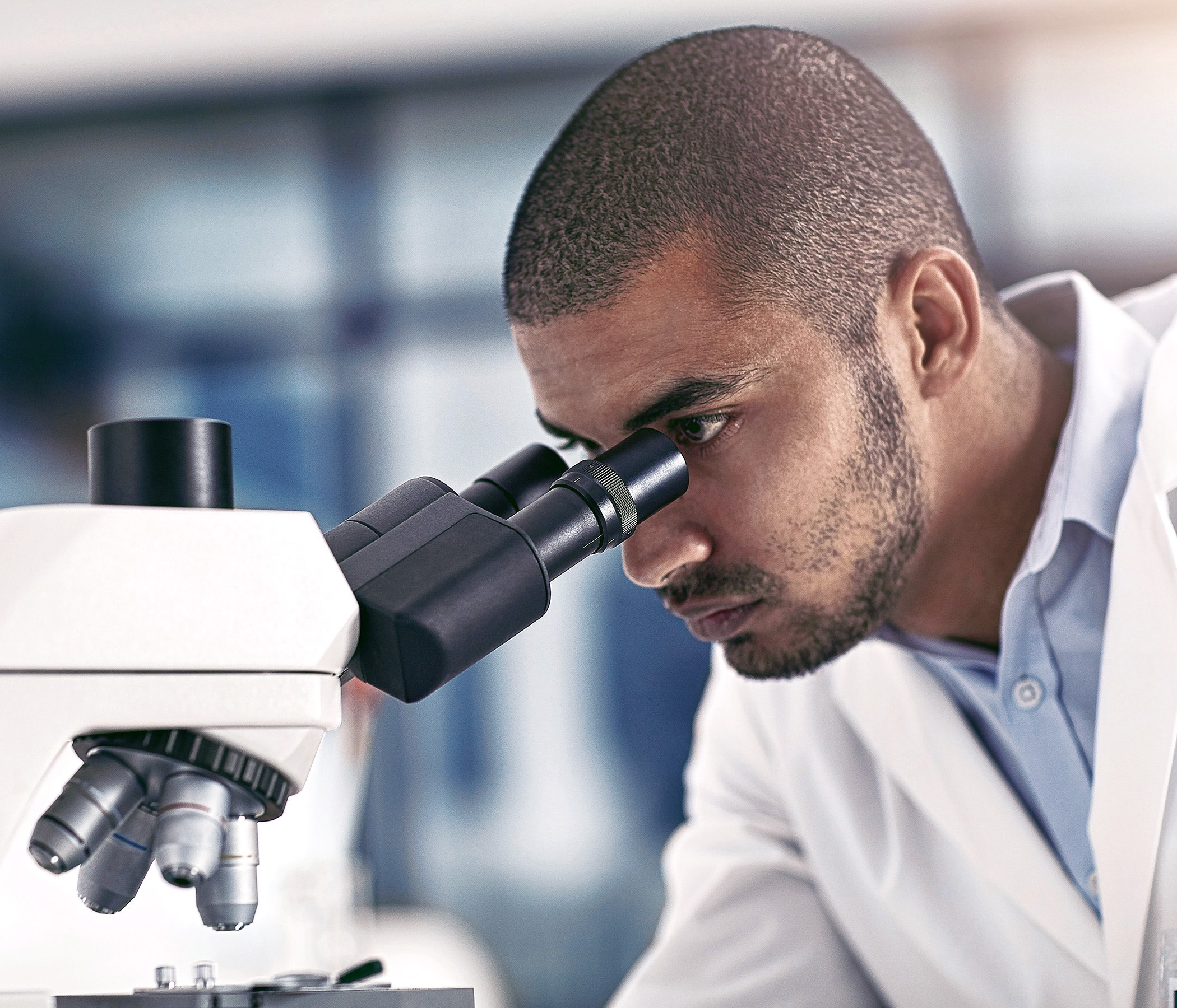 young male scientist working in his lab looking into microscope