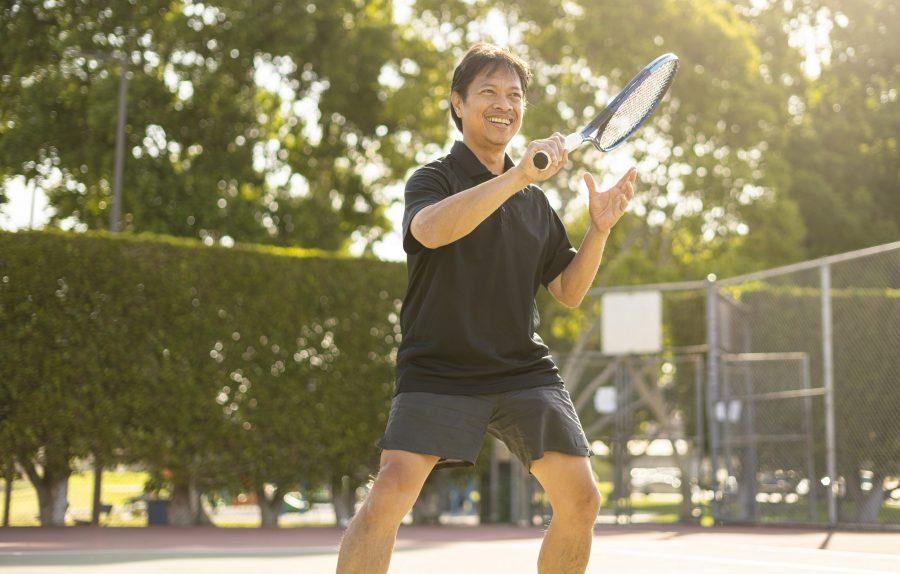 Hombre maduro que juega al tenis que golpea el primer de la bola