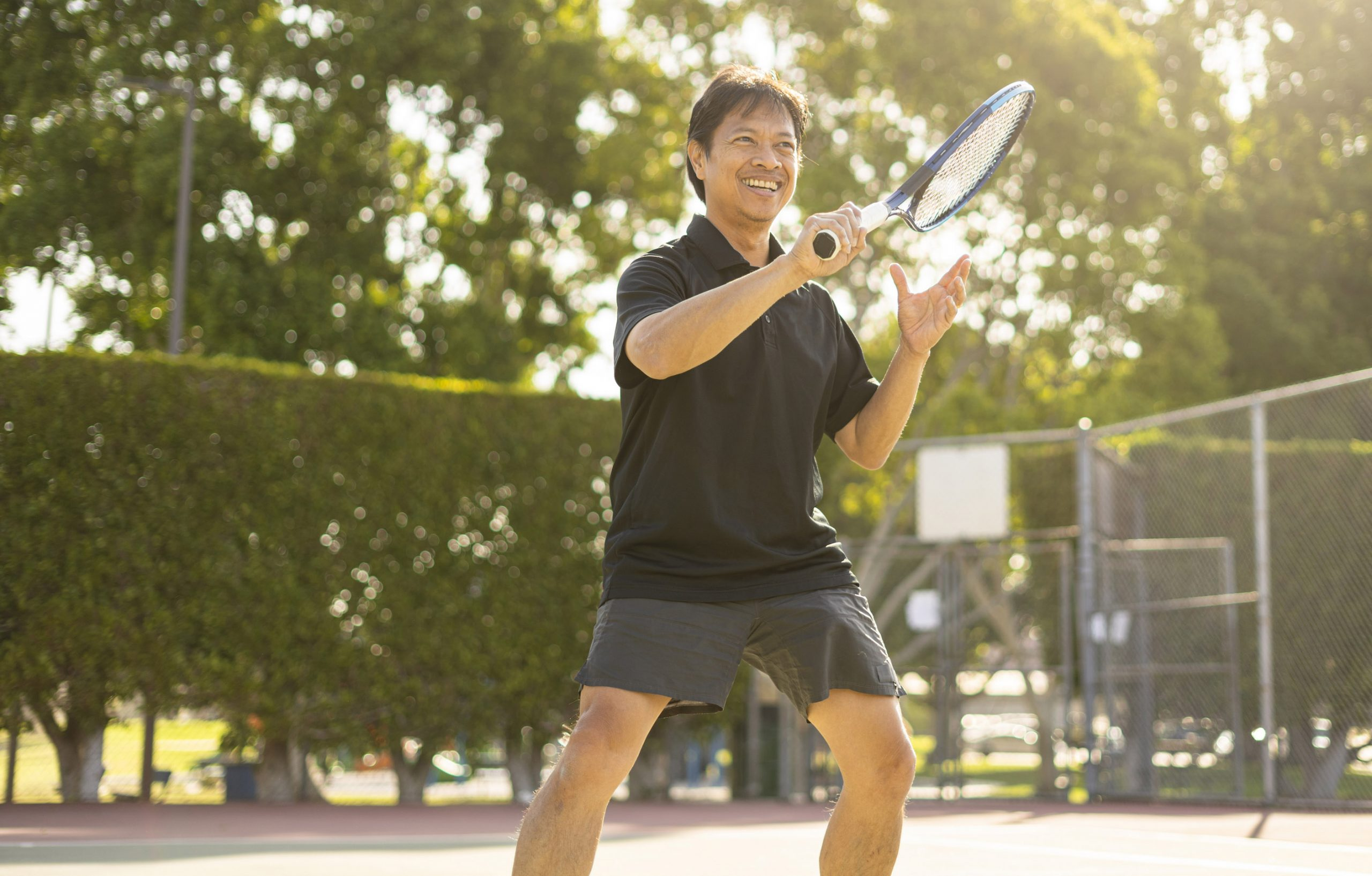 Mature man playing tennis hitting the ball closeup