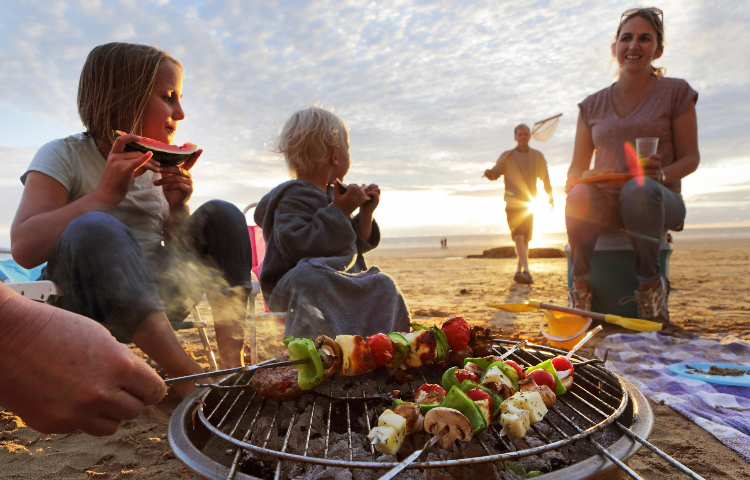 A family is enjoying grilling kebabs together on the beach as the sun begins to set.