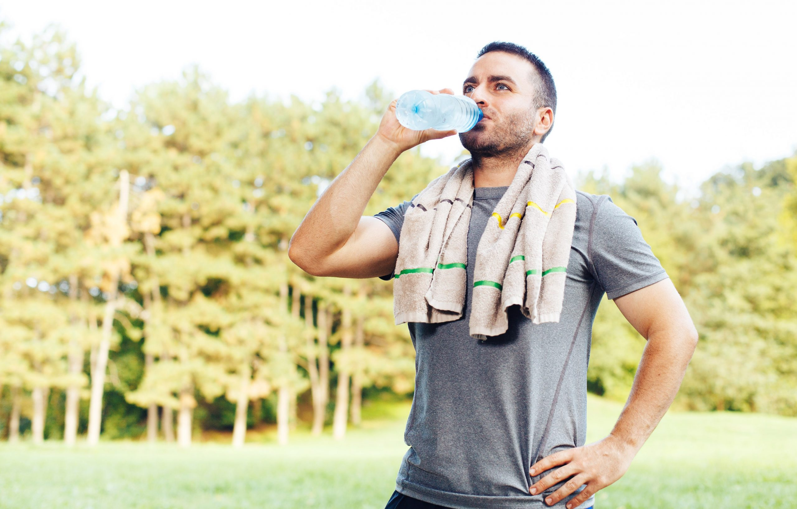 Young man drinking water after workout