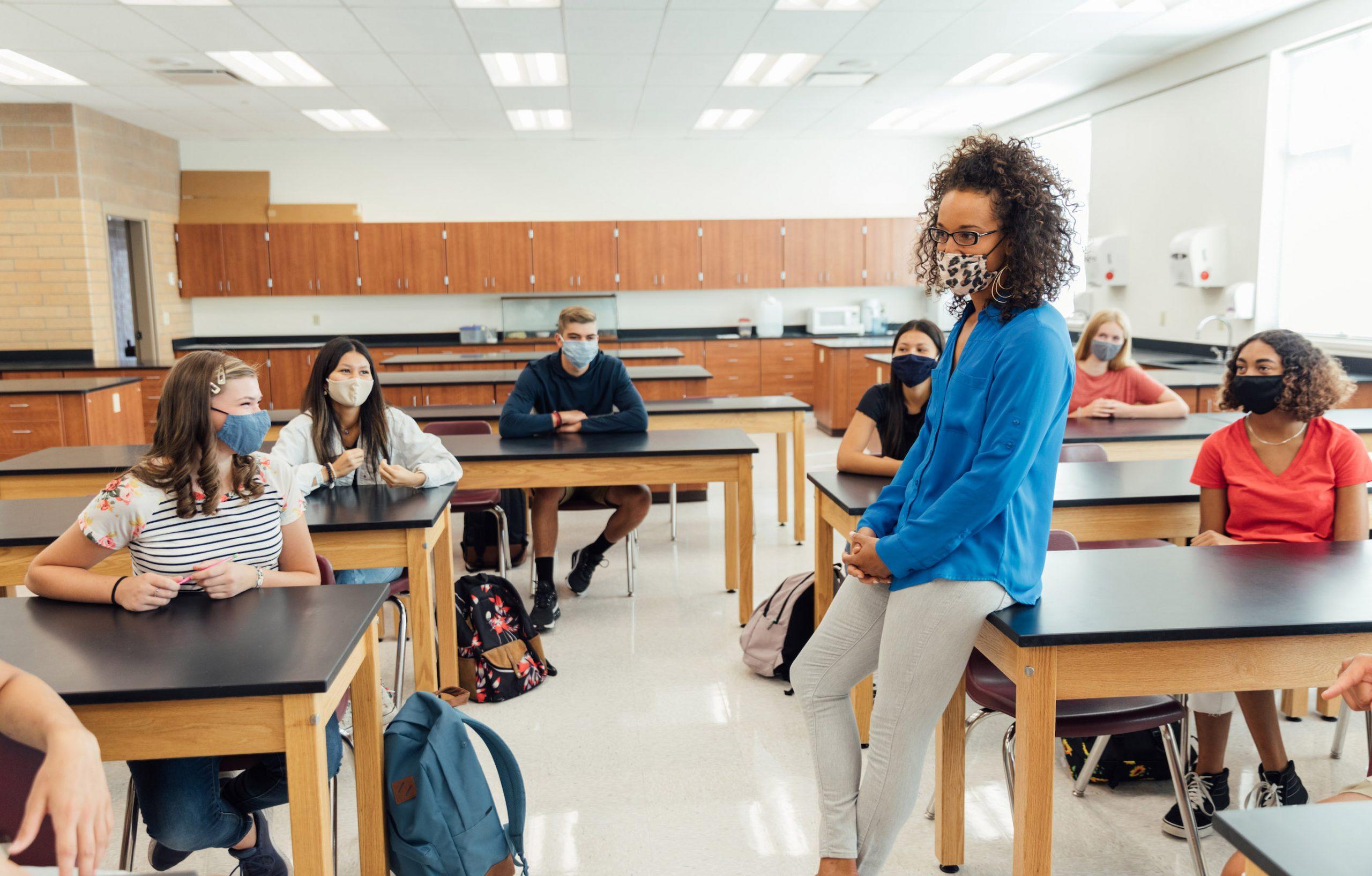 Profesor enmascarado de la High School secundaria que se dirige a estudiantes en sala de clase