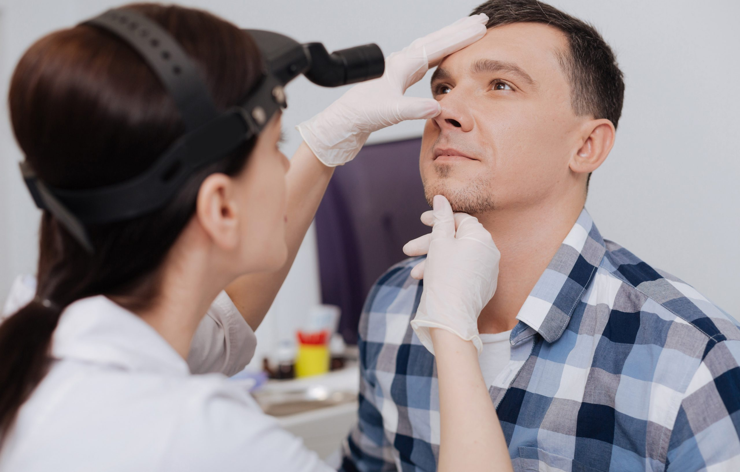 Doctor looking at nose of her visitor